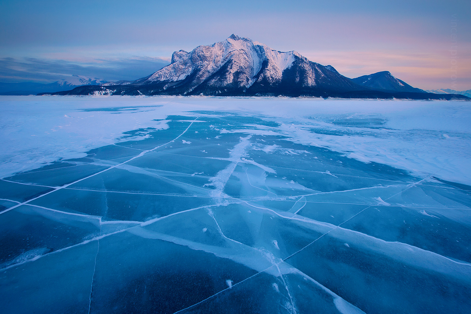 A shot of Abraham Lake in the winter with giant cracks in the blue ice leading up to a mountain.