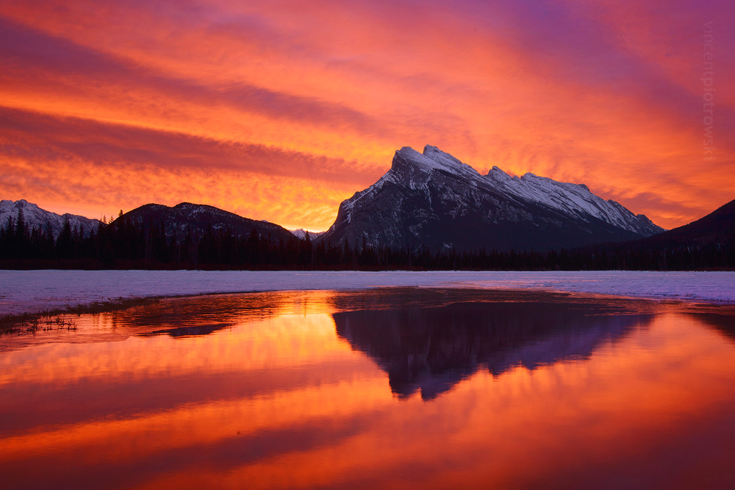 Sunrise captured on Vermillion Lakes with Mt Rundle reflected in the water with intense colours.