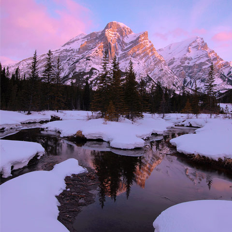 A landscape featuring Mt Kidd in Kananaskis Country with reflecting pools surrounded by snow during a cold morning sunrise