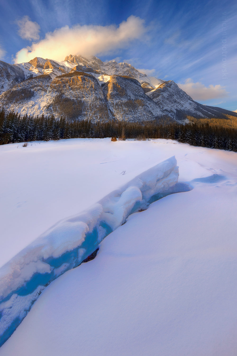 A photograph of a crack in the thick ice of Cascade Ponds leading up to Cascade Mountain in Banff National Park.