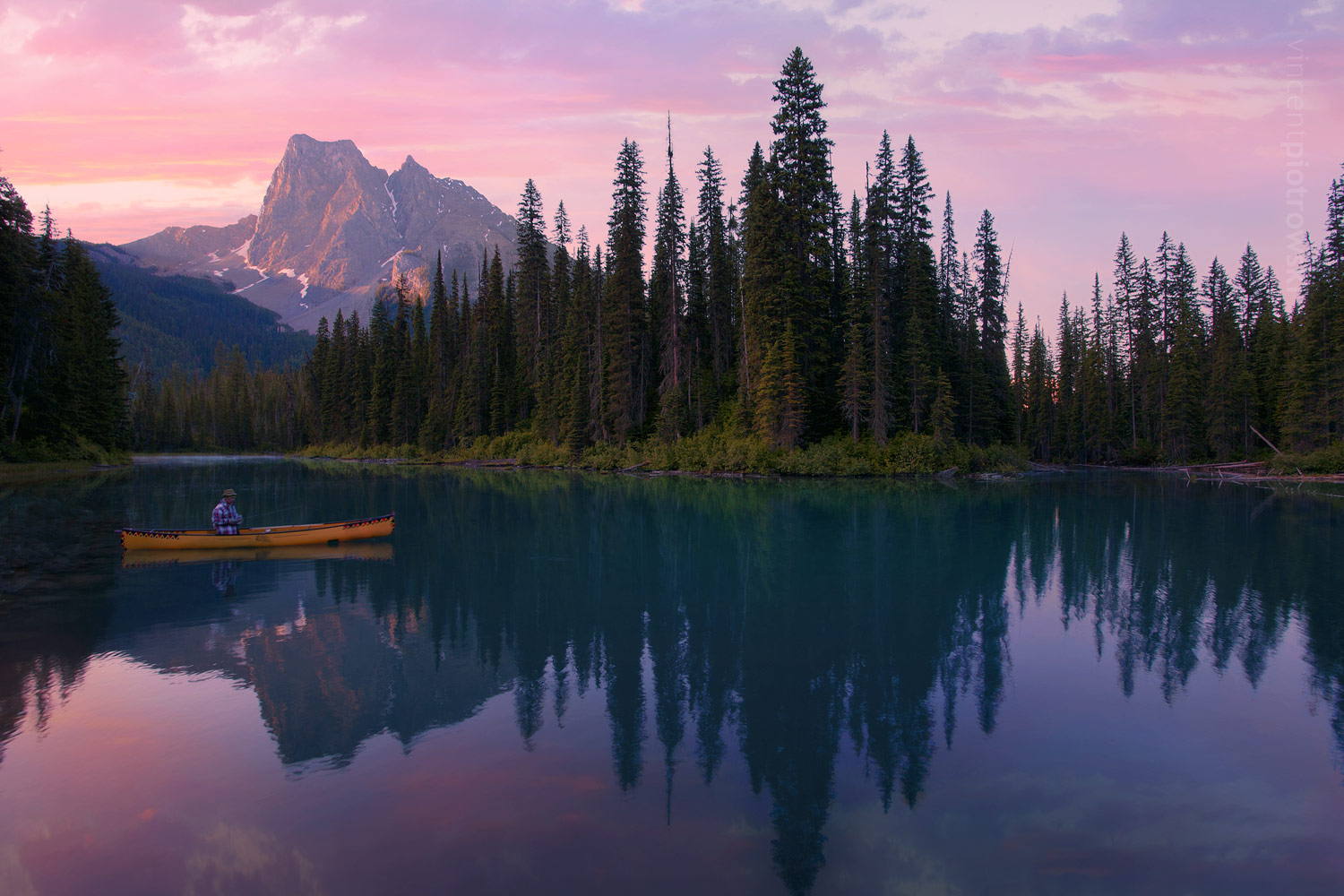 A sportsman fishing out of a canoe on Emerald Lake at sunrise with mountains in the background.