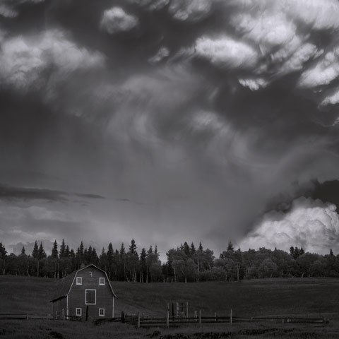 A giant mushroom clouds of a supercell storm rising over a barn in the Foothills of Alberta.