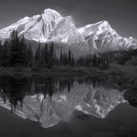 A black and white photo of Mt Kidd reflected in Wedge Pond with lots of contrast between the sky and snow on the mountain tops.