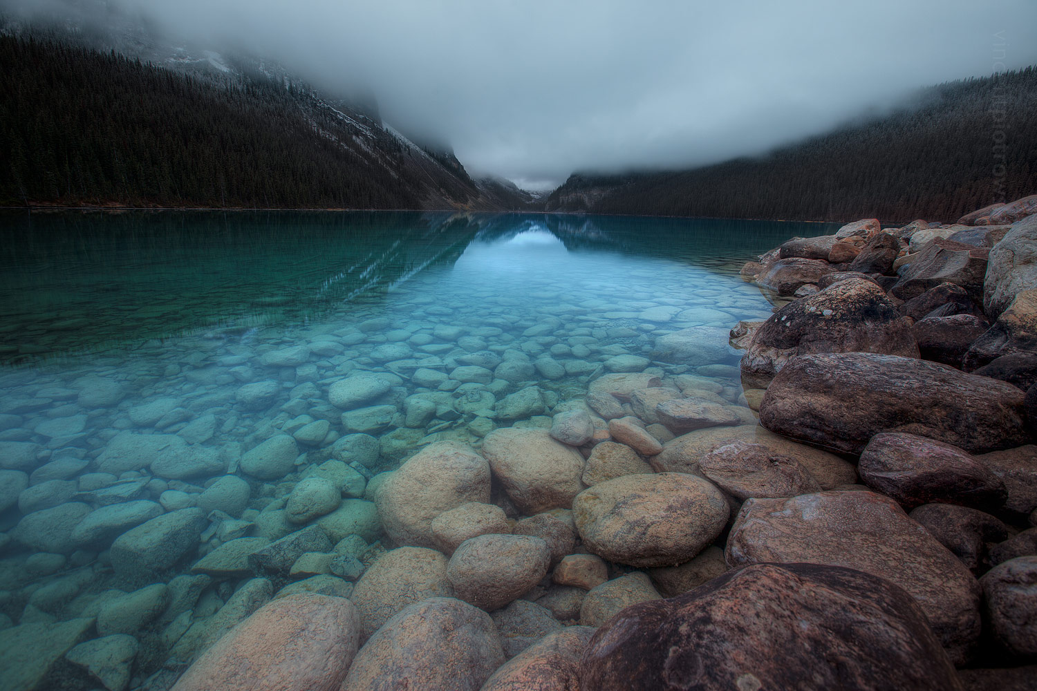A landscape photo of Lake Louise in Banff National Park taken on a very overcast day with low hanging cloud that enhances the colour of the turquoise water.