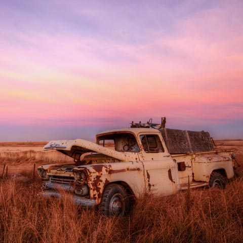 A picture of a rusted out 59 Chevy truck in the middle of the prairies taken at sunset