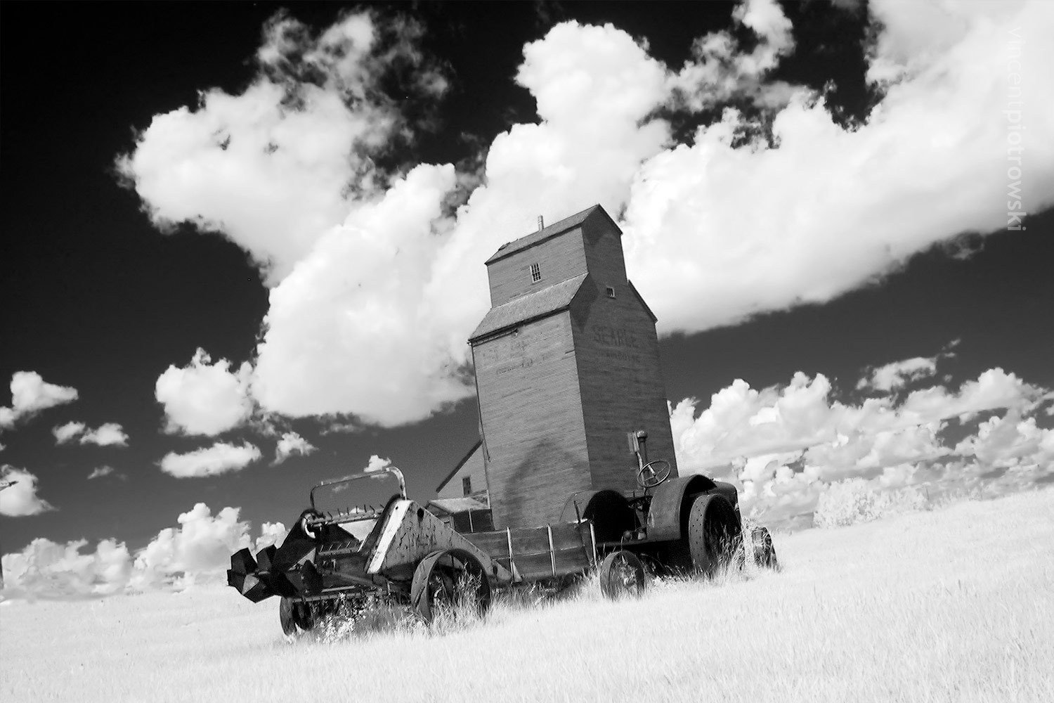 A picture of the grain elevators in Rowley Alberta taken with an infrared filter with a tractor in the foreground.