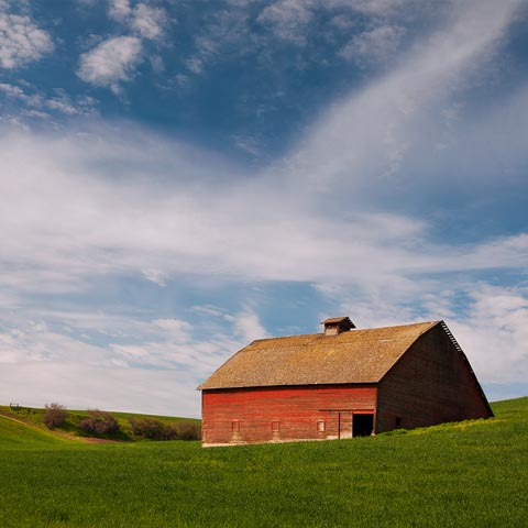 A picture of a red barn under a blue sky with crazy clouds and green fields