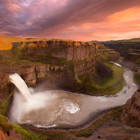 A wide angle photograph of Palouse Falls and the sorrounding canyons taken using long exposure to show the currents in the water