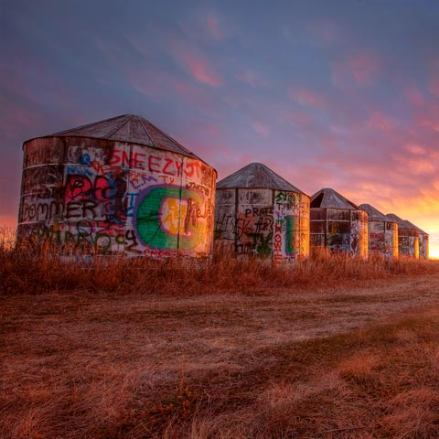 A picture of some vandalized wooden grain silos taken near Calgary Alberta during an incredible sunrise