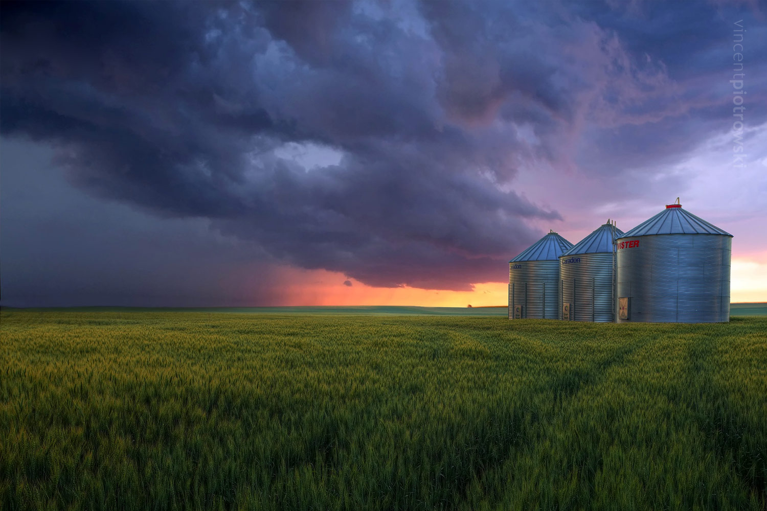 A photograph of metal grain silos taken near Drumheller Alberta with dark storm clouds on the horizon and the sun peaking through