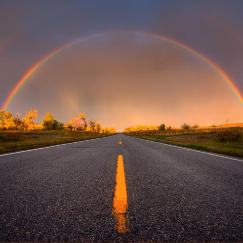 A picture of a double rainbow following a prairie storm over top of a paved road with a yellow stripe taken near Ft McLeod Alberta