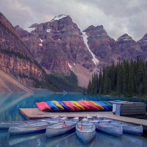 A picture of Moraine Lake in Banff National Park Canada on a cloudy evening that enhanced the colour of the blue water and make the rows of canoes and kayaks look extra bright